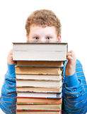 Surprised boy looks out from behind a pile of books. Surprised boy looks out from behind a stack of books on white background Royalty Free Stock Image