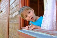 The surprised boy looks out of the window. Little boy with surprised looks out of the window of a wooden house Royalty Free Stock Images