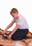 Surprised boy opening a box. Amazed kid sitting on a carpet and opening a tiny wooden chest Royalty Free Stock Photography