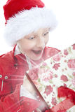 Surprised boy opening present over white Stock Images