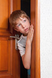 Surprised boy peeks from behind door Stock Photography