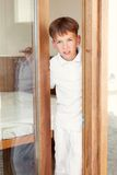 Surprised boy peeks from behind door Royalty Free Stock Photos