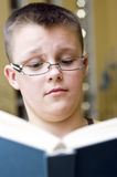 Surprised boy reading a book. A clever teenage boy wearing glasses, reading a book. Surprised  and disbelieving expression on his face Stock Photography