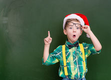 Surprised boy in red christmas hat near a green chalkboard showi Royalty Free Stock Image
