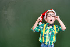 Surprised boy in red christmas hat near a green chalkboard showi Stock Images
