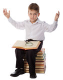 Surprised boy sitting on pile of books with magnifyer Royalty Free Stock Photo