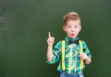 Surprised boy stands near the chalkboard Stock Image
