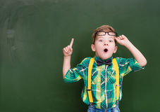 Surprised boy stands near empty chalkboard and showing finger up Royalty Free Stock Photography