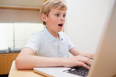 Surprised boy using a notebook Stock Photos