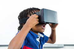 Surprised boy using virtual reality headset in classroom. Surprised boy using virtual reality headset while sitting in classroom Royalty Free Stock Photos