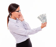 Surprised brunette businesswoman looking at money Royalty Free Stock Image