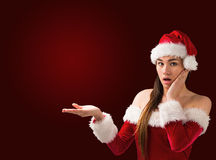 Surprised brunette in santa outfit presenting with hand Royalty Free Stock Photography