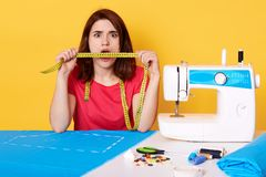 Surprised brunette seamstress holding measure tape in front of her mouth, looking directly at camera. Sewing machine, piece of stock photography