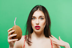 Surprised Brunette with Tropical Cocktail in Hands on Green Background. Stock Photo