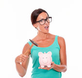 Surprised brunette woman holding piggy bank Royalty Free Stock Photos
