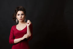 Surprised brunette woman with perfect make up and stylish haircut posing. Emotionally girl wearing red dress and big earrings gest Stock Images