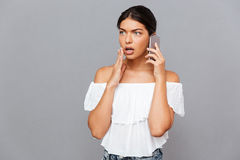 Surprised brunette woman talking on the phone Stock Photo