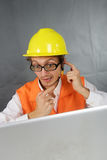 Surprised builder with computer. Surprised young builder with laptop. Vertical photo Stock Images