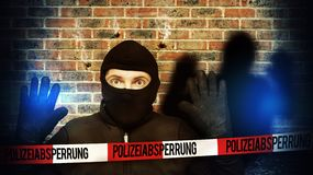 Surprised burglar stopped because of blue police light and take his hands up.  Stock Image