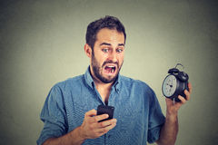 Surprised business man with alarm clock looking at smart phone Royalty Free Stock Image