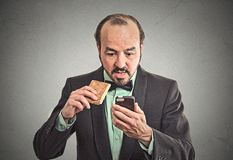 Surprised business man eating on a go cookie using smartphone Stock Photo