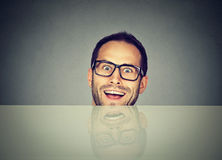 Surprised business man hiding under table royalty free stock photos