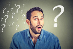 Surprised business man with many question Royalty Free Stock Images