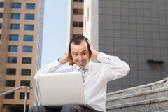 Surprised business man sitting on steps with laptop hods his hea Stock Photo