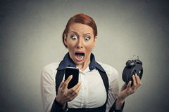 Surprised business woman with alarm clock looking at smart phone. Portrait surprised business woman with alarm clock looking at smart phone with funny face royalty free stock images