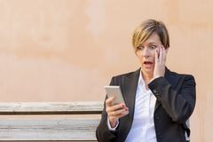 Surprised business woman calling by phone outdoor Royalty Free Stock Image