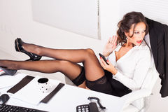 Surprised business woman. Hot business woman sitting in the office with legs on the table, typing sms on mobile phone with surprised looking Royalty Free Stock Images