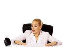 Surprised business woman looking at alarm clock behind the desk Royalty Free Stock Image