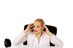 Surprised business woman looking at alarm clock behind the desk Royalty Free Stock Photos