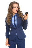 Surprised business woman looking on cell phone Royalty Free Stock Images