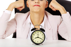 Surprised business woman lsitting behind the desk with alarm clock Stock Image