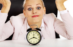 Surprised business woman lsitting behind the desk with alarm clock Stock Photo