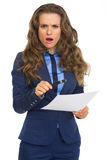 Surprised business woman with magnifying glass and document Royalty Free Stock Photography