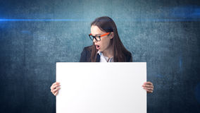 Surprised Business woman portrait with blank white board on blue  . Female model with long hair in glasses. Stock Photos