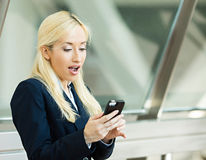 Surprised business woman reading something on her smart phone. Closeup portrait pretty young, blonde woman looking shocked with opened mouth and eyes on cell Royalty Free Stock Image