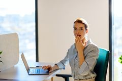 Surprised business woman sitting at the desk in office. stock photo