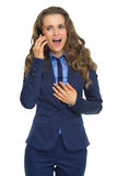 Surprised business woman talking cell phone. Isolated on white Stock Images