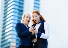 Surprised business women looking at smart phone, receiving unexp Stock Photo