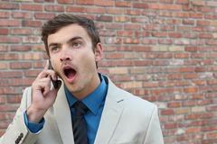 Surprised businessman in a beige suit with a mobile phone with lots of copy space stock images