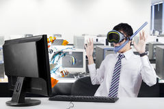 Surprised businessman with fishes on the monitor. Male entrepreneur wearing goggles and snorkel in the office, looks surprised while looking at fishes coming out Stock Photography