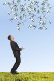 Surprised businessman and flying dollar. Banknotes against blue sky Stock Image
