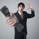 Surprised businessman giving handset. Portrait of a young businessman giving handset with a surprised expression on her face Royalty Free Stock Photos