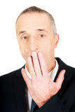 Surprised businessman with hand on mouth Stock Photo