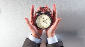 Surprised businessman hands holding an alarm clock for time strategy Royalty Free Stock Image