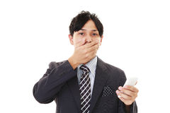 Surprised Businessman holding a smart phone Royalty Free Stock Photo