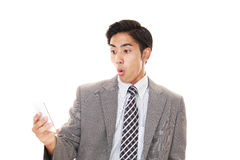 Surprised Businessman holding a smart phone Royalty Free Stock Photos